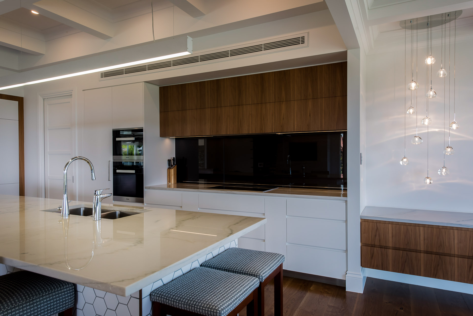 kitchen, black glass splashback, lift up splashback, white granite, miele ovens, minka joinery